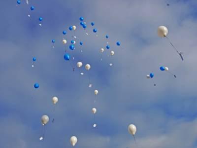 Fliegende Luftballons in blau und weiß.