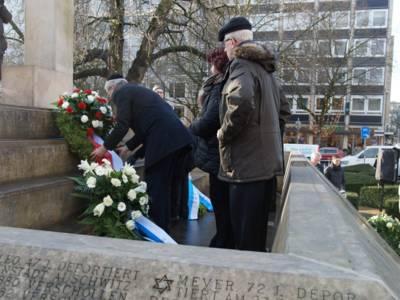 Menschen stehen vor einem Holocaust-Mahnmal und legen Blumenkränze nieder.