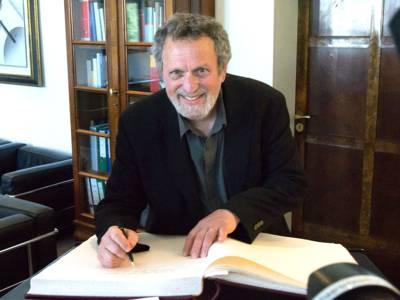Lächelnder Mann, der sich in ein Buch einträgt.