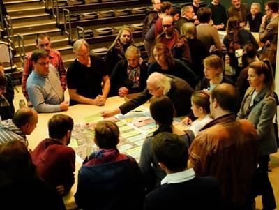 Eine Gruppe Menschen, die um einen Tisch sitzen und auf einen Stadtplan blicken.