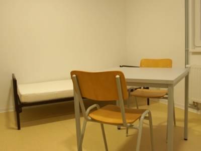 Kleines Zimmer mit einem Bett und zwei Stühlen.