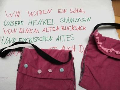 Zwei Taschen auf einem Stück Tapete. Auf der steht: Wir waren ein Schal, unsere Henkel stammen von einem alten Rucksack und ein bisschen Altes...