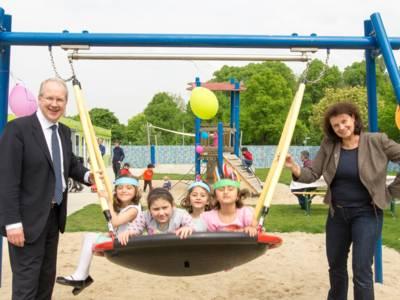 Oberbürgermeister Stefan Schostok und Bildungsdezernentin Rita Maria Rzyski, die Kinder beim Schaukeln anschubsen.