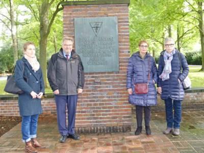 Ein Mann und drei Frauen stehen vor einem Mahnmal.