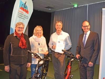 Eine Gruppe aus zwei Männern und zwei Frauen, die nebeneinander stehen, zwischen ihnen stehen zwei Fahrräder.