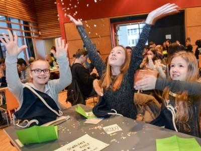 Schülerinnen und Schüler sitzen in Kleingruppen an Tischen, die verstreut im Raum aufgestellt sind. Im Vordergrund drei Mädchen, die Papierschnitzel in die Luft werfen.