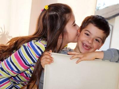 Zwei Kinder in häuslicher Umgebung: Die Schwester gibt ihrem Bruder einen Kuss.