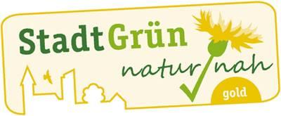 """Das Label """"StadtGrün naturnah"""" zeigt außer diesen Worten eine gezeichnete Stadtsilhouette, über der ein Vogel fliegt, und eine Blume im Großformat."""