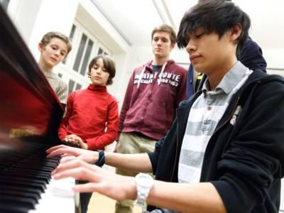 Junge Menschen beim Klavierunterricht.