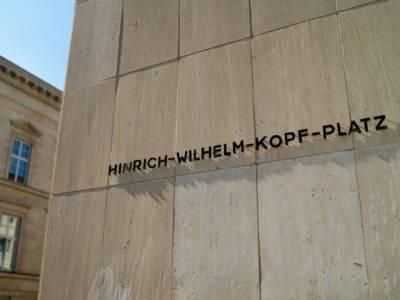 """Der Schriftzug """"Hinrich-Wilhelm-Kopf-Platz"""" an einer Häuserfassade."""