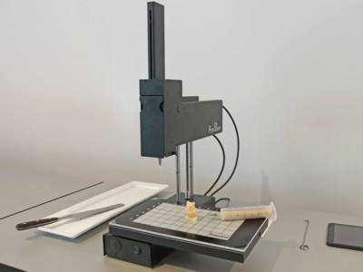 Ein 3D-Drucker mit einer kleinen Eule davor.
