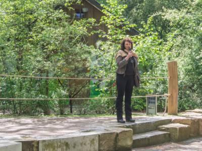 Frau mit Mikrofon in einem Wald.