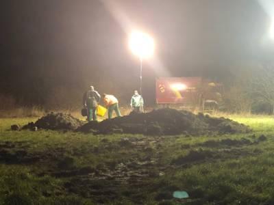 Drei Menschen um einen Erdhügel auf einem beleuchteten Feld.