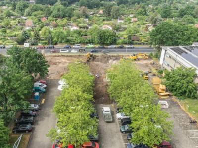 Baustelle auf einem Parkplatz aus der Vogelperspektive, im Hintergrund Kleingärten