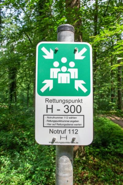 """Schild im Wald, auf dem """"Rettungspunkt H - 300"""" steht."""