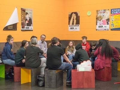 Erwachsene und Jugendliche in einer Gesprächsrunde.