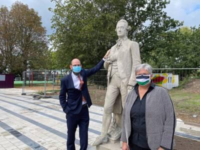 Ein Mann und eine Frau stehen um eine Statue, dahinter ein Bauzaun.