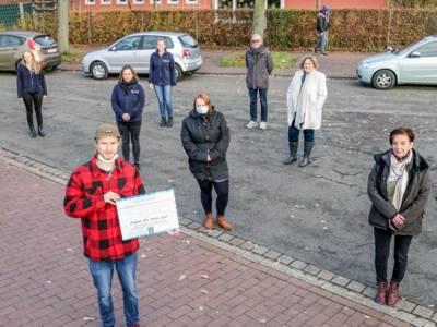 Mehrere Personen auf einer Straße. Sie stehen mit Abstand zueinander. Einer hält eine Urkunde.