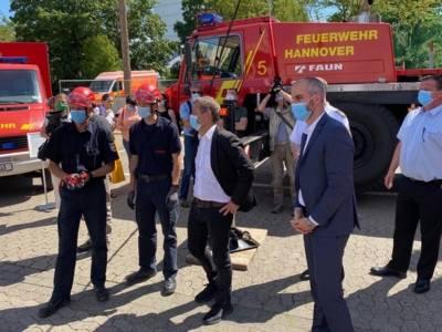 Mehrere Personen mit Masken vor Feuerwehr-Fahrzeugen.