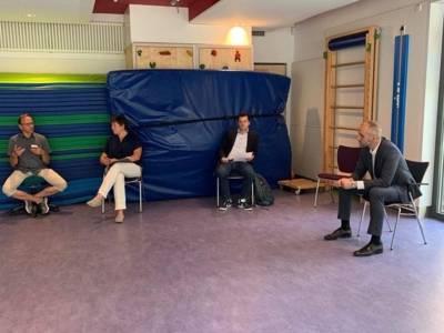 Vier Personen im Gespräch. Sie sitzen in einem Saal und halten Abstand.