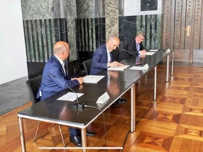 Drei Männer an einem Tisch bei der Unterzeichnung eines Vertrages.