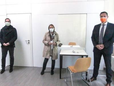 Drei Personen mit Mund-Nasen-Schutz in einem Raum.