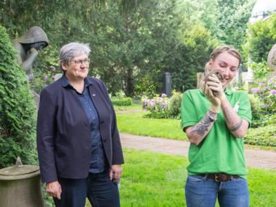 Zwei Frauen stehen auf einem Friedhof, eine der beiden hält einen Igel in den Händen
