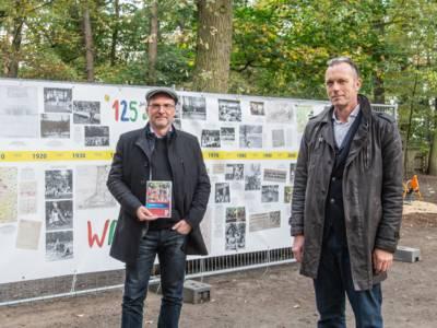 Zwei Männer stehen vor einem großen Banner, auf dem ein Zeitstrahl zu sehen ist