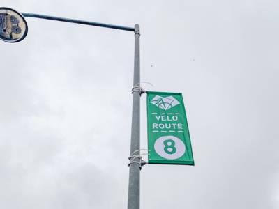 """Eine Fahne mit der Aufschrift """"Veloroute"""" an einem Laternenmast"""