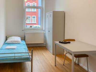 Blick in ein Zimmer, in dem ein Bett, ein Tisch, ein Stuhl sowie ein Spind stehen