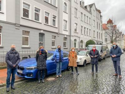 Sechs Personen stehen mit Masken und Abstand zueinander auf einer Straße vor einem Haus