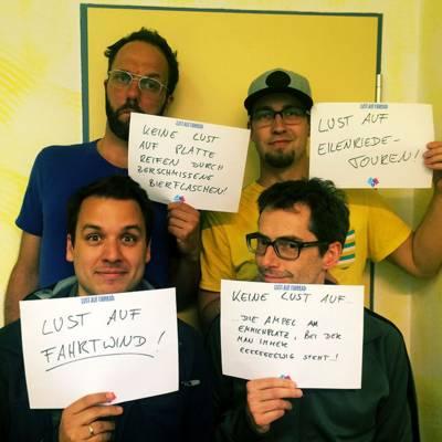 Vier Männer, die selbst beschriebene Schilder halten