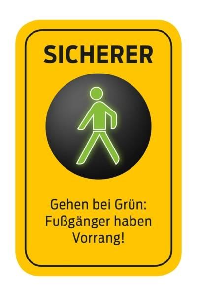 """Ein Piktogramm mit folgendem Text: """"SICHERER - Gehen bei Grün: Fußgänger haben Vorrang"""""""