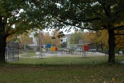 Spielplatz, im Bildvordergrund Grünfläche mit Bäumen