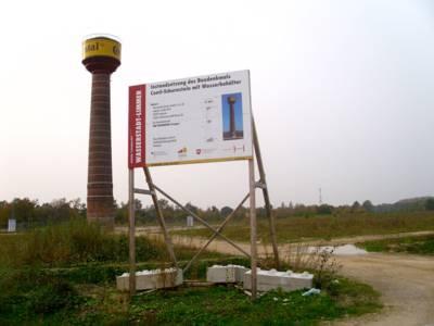Conti-Schornstein mit Wasserbehälter, im Bildvordergrund ein Bauschild
