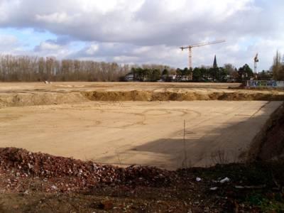 Gewalzter Sandboden auf der Baustelle, im Bildhintergrund ein großer Kran