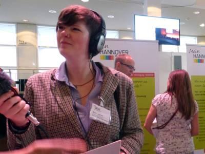 Eine junge Frau interviewt einen Veranstaltungsbesucher.