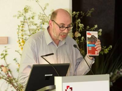 Friedhelm Hagen vom Fachbereich Soziales der Landeshauptstadt hält am Rednerpult eine Broschüre zum Thema Wohngeld in die Höhe