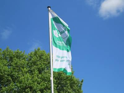"""Die grün-weiße """"Bürgermeister für den Frieden""""-Flagge mit einer weißen Taube und dem Wort """"Peace"""" weht im Wind vor blauem Himmel."""