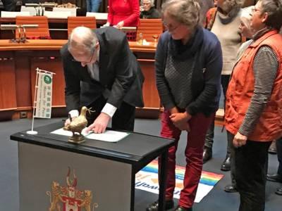 Auf einem Tisch im Hodlersaal, der mit einer Mayors-for-Peace-Fahne versehen ist, unterzeichnet der Oberbürgermeister ein Dokument.
