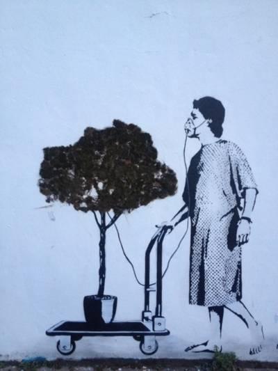 Auf einer Häuserwand ist eine barfuß gehende Frau in Patientenkleidung mit Atemschutzmaske gezeichnet, die ein Bäumchen auf einem Rollwagen vor sich herschiebt, von dem aus ein Schlauch mit Sauerstoff zur Atemmaske der Frau führt.
