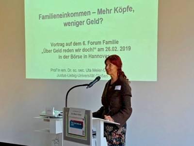 """Prof. em. Dr. oec. Uta Meier-Gräwe am Redepult; dahinter ist der Beginn der Power Point Präsentation """"Familieneinkommen: Mehr Köpfe, weniger Geld"""" an eine Leinwand projiziert."""