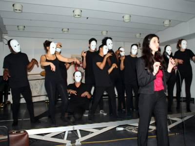 Eine Jugendliche steht vor der Bühne des VHS-Saals und spricht in ein Mikrofon. Hinter ihr stehen etwa 12 weitere Personen, die allesamt neutrale Masken vor dem Gesicht tragen und ihre Arme nach vorne strecken.