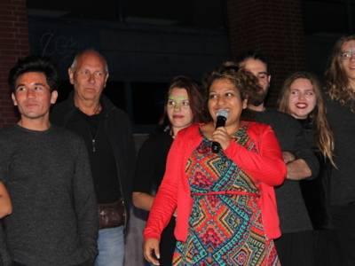 Zwei Erwachsene und fünf Jugendliche stehen nebeneinander auf der Bühne. Die Frau in der Mitte spricht in ein Mikrofon.