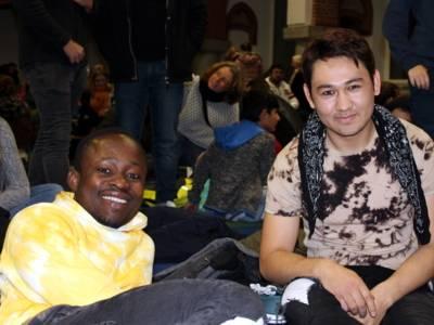 Zwei Jungen sitzen auf Sitzmatten und blicken nach vorn. Der Linke stützt sich mit dem Arm ab.