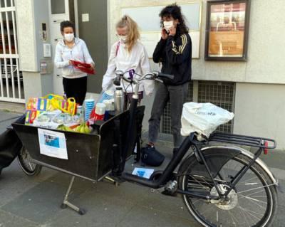 Drei Frauen stehen mit Schutzmasken hinter einem beladenen Lastenfahrrad.