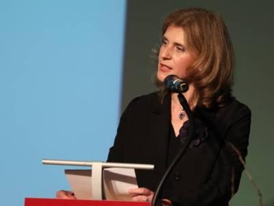 Eine Frau steht auf der Bühne des Hauses der Religion an einem Redner*innenpult und spricht in ein daran montiertes Mikrofon.