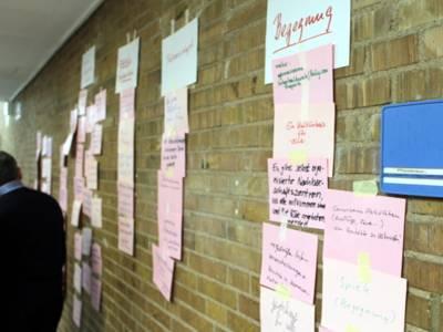An einer Backsteinwand hängen unter sieben Papieren mit Themenbeschreibungen in vertikalen Reihen handschriftliche Gedanken und Argumente auf einzelnen, kleineren Zetteln.