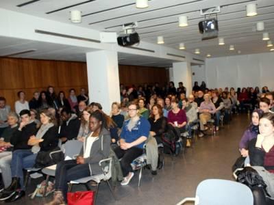 Etwa 100 Personen sitzen in zwei Stuhlblöcken und schauen nach vorne. Weitere 50 stehen am Rand und blicken ebenfalls in Richtung Bühne.