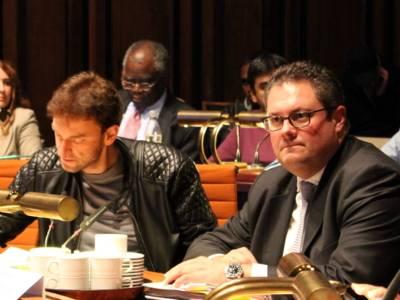 Zwei Männer sitzen im Hoflersaal hinter Pulten. Der Linke blickt auf Unterlagen, die auf seinem Tische liegen, der Rechte blickt nach vorn.